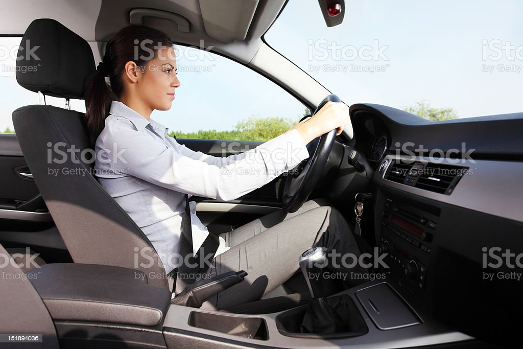 Business woman sitting behind the wheel and driving. royalty-free stock photo