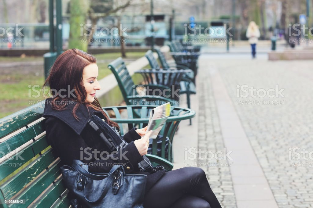 Business woman sitting on bench reading newspaper, city business stock photo