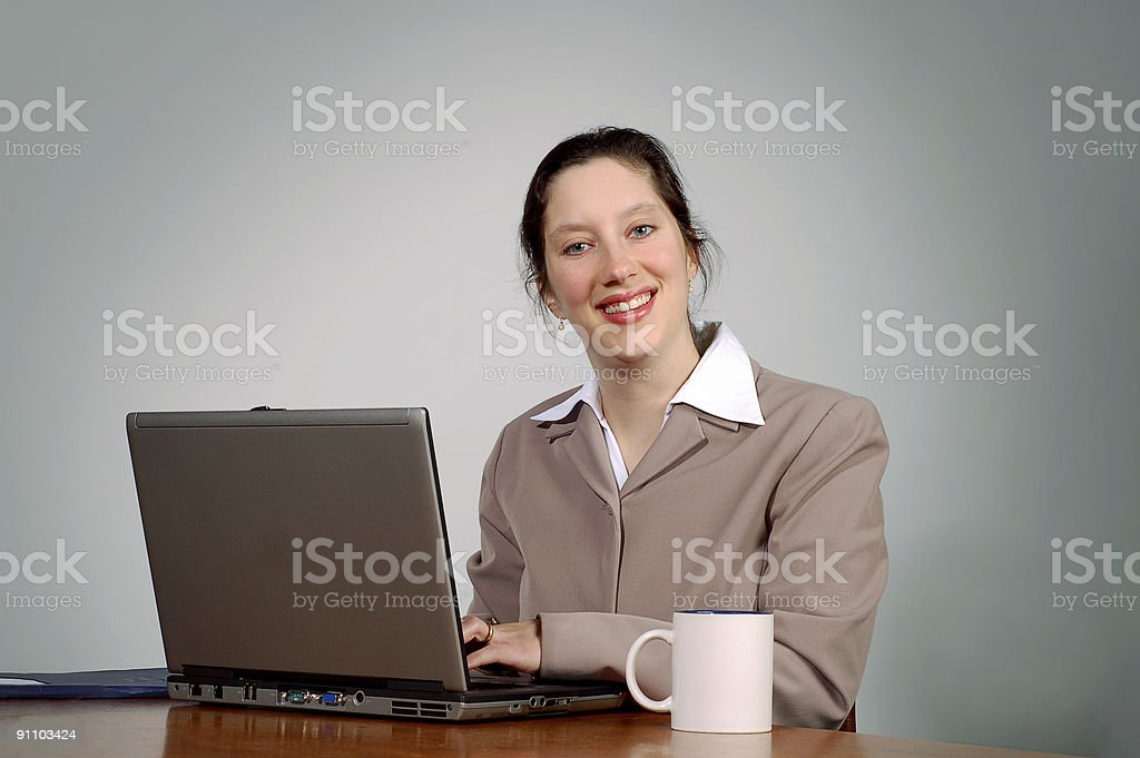 Business woman smiles while typing royalty-free stock photo