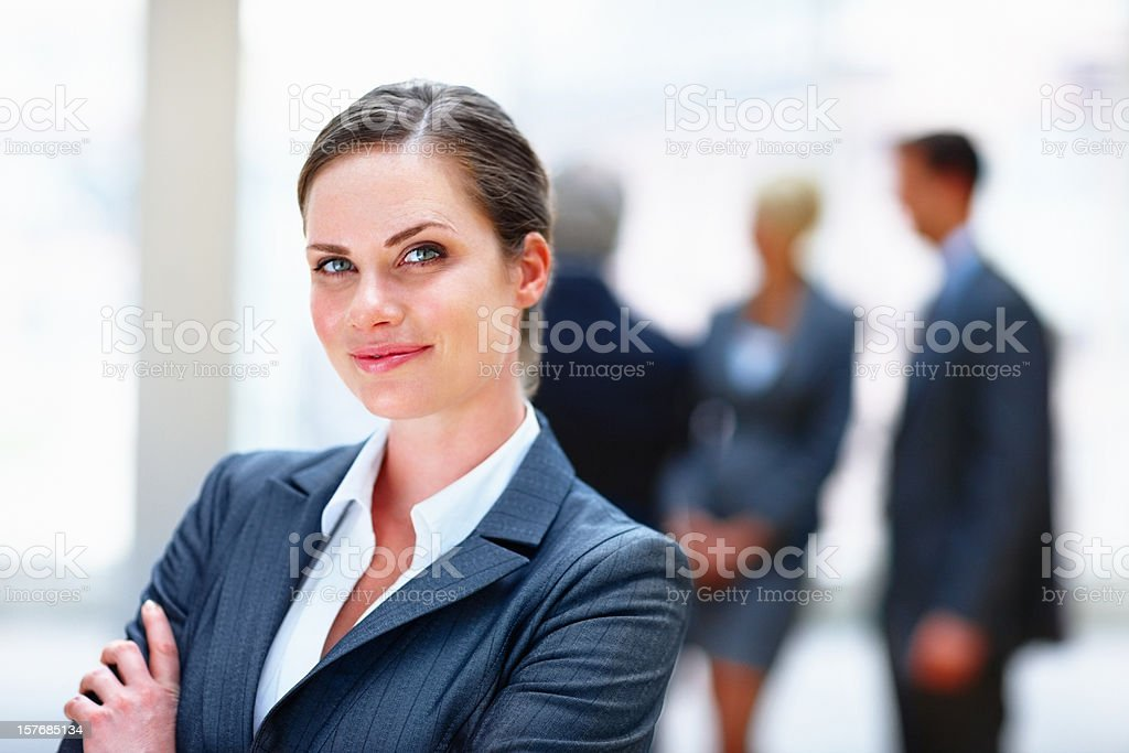 Business woman smiling with team in the background royalty-free stock photo