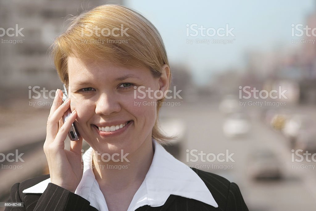 business woman speaks by phone in the street stock photo