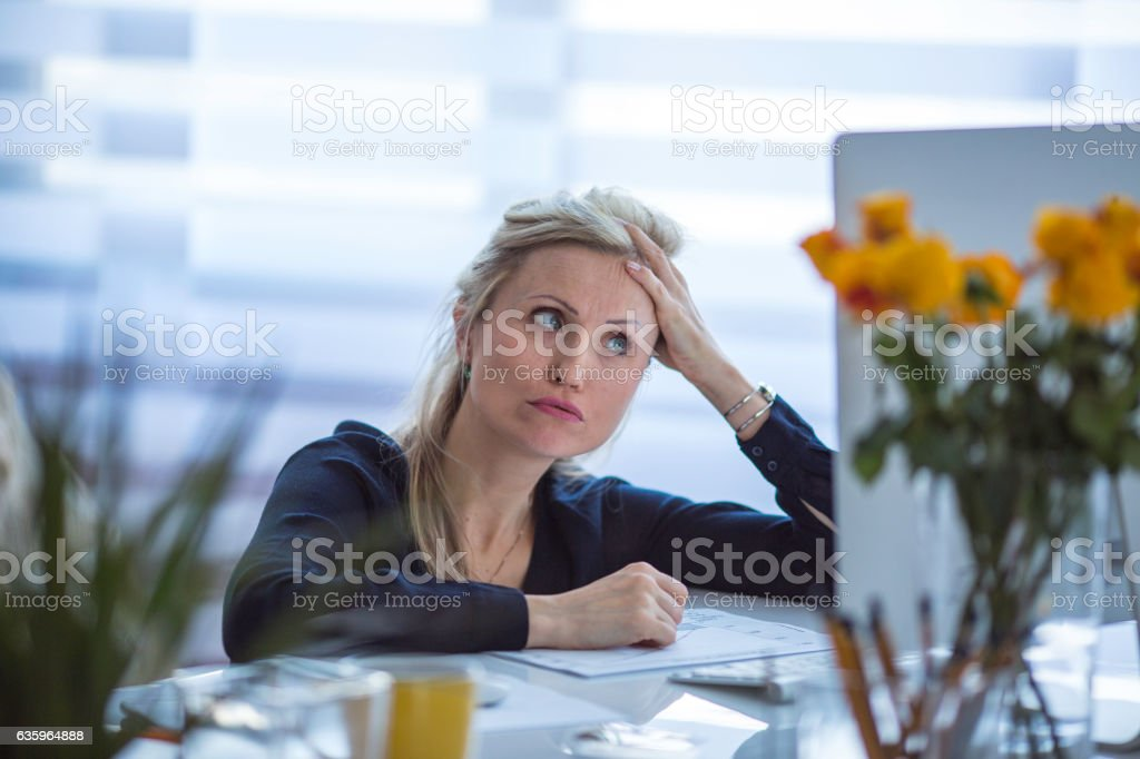 Business woman squatting next to the table stock photo