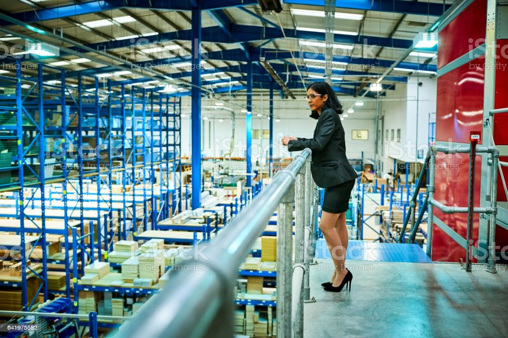 Business woman standing in factory balcony stock photo