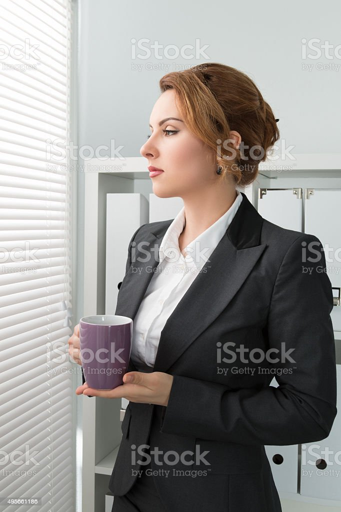 business woman standing near the window and looking outside with stock photo
