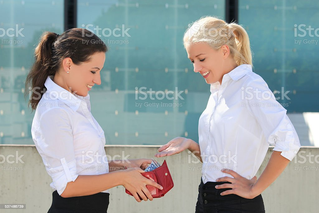 business woman taking euro banknotes out from wallet and giving stock photo