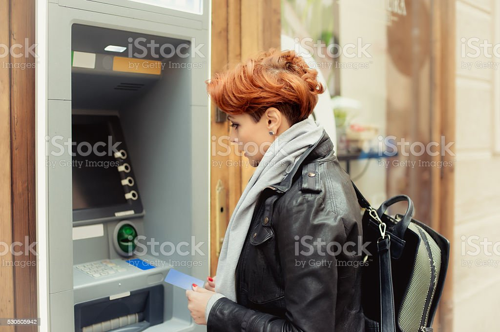 Business woman taking money from ATM stock photo