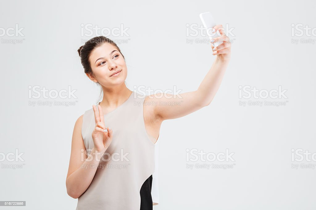 Business woman taking selfie with smartphone and showing peace gesture stock photo