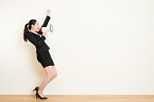 business woman talking in megaphone with white wall