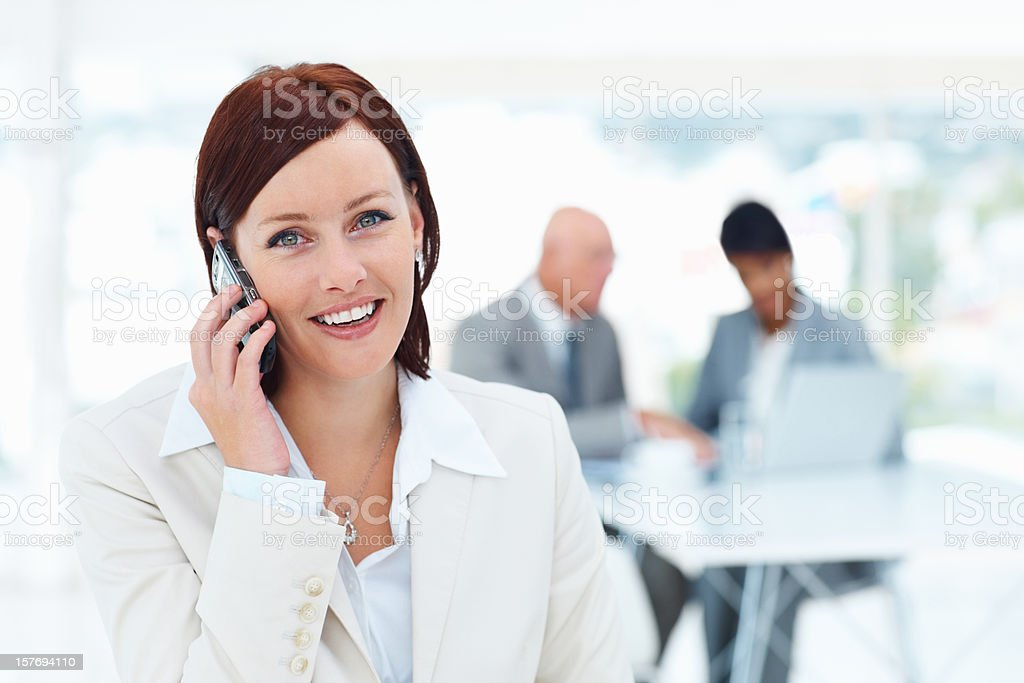 Business woman talking over cellphone with her team in background royalty-free stock photo