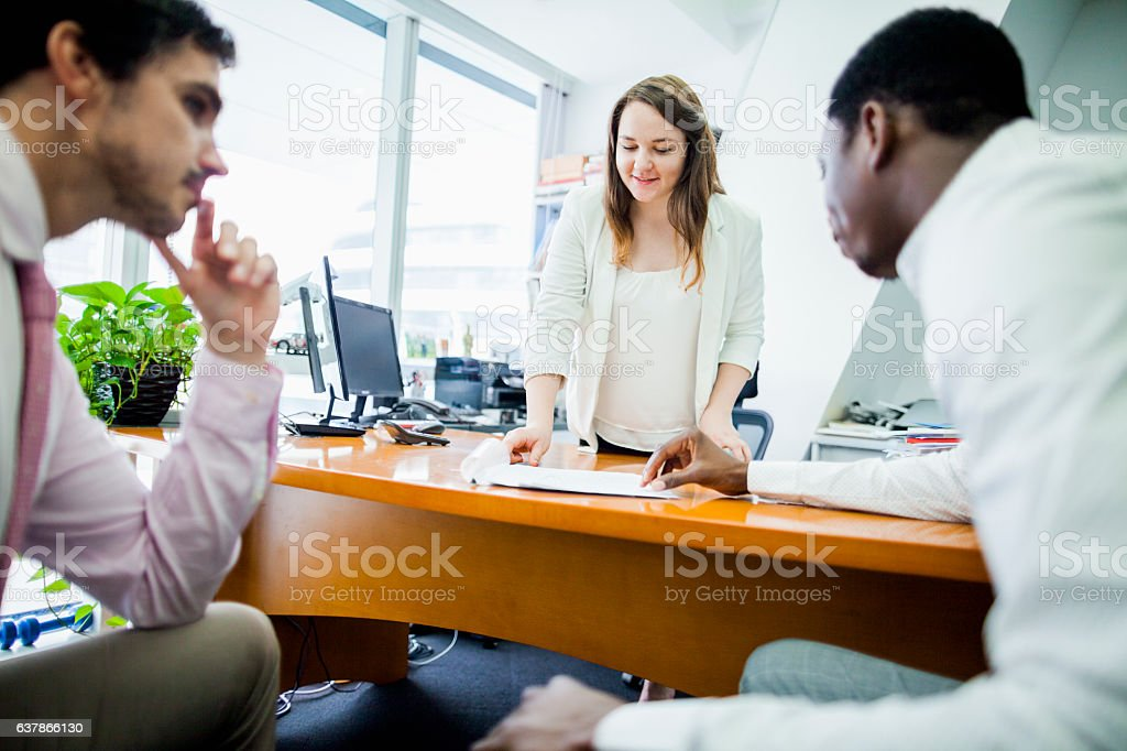 Business woman talking with colleagues in office stock photo