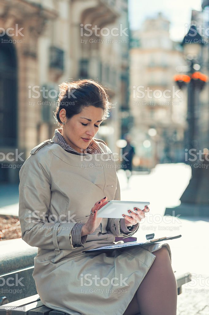 Business woman taping on the tablet while sitting stock photo
