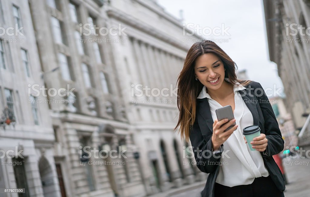 Business woman texting on her mobile phone while walking on the...