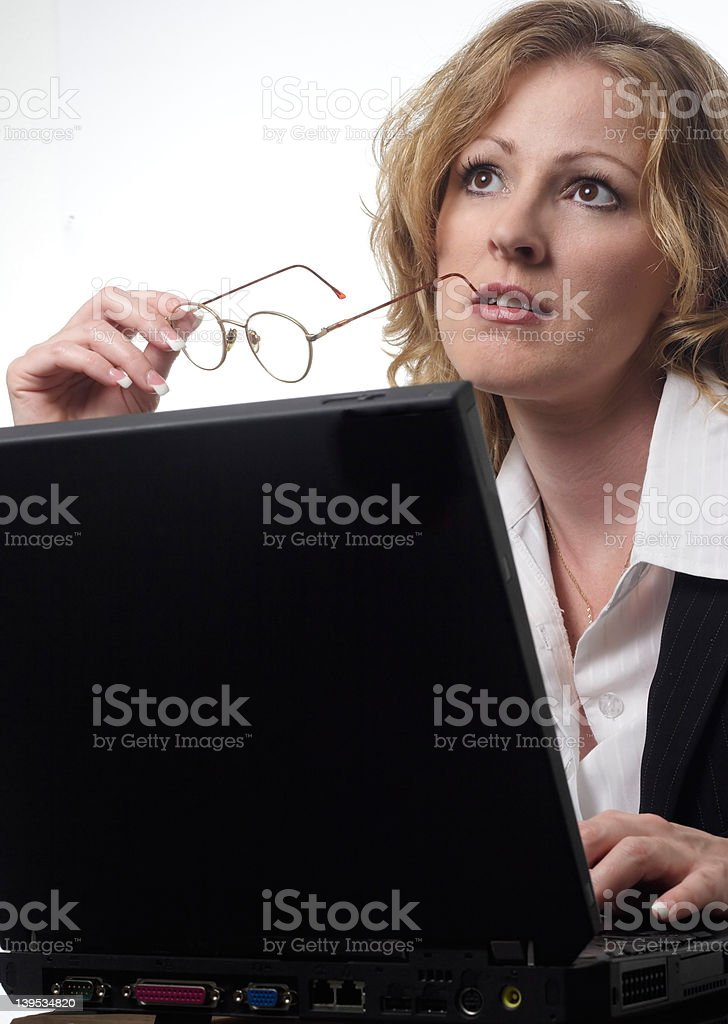 Business woman thinking while working on laptop stock photo