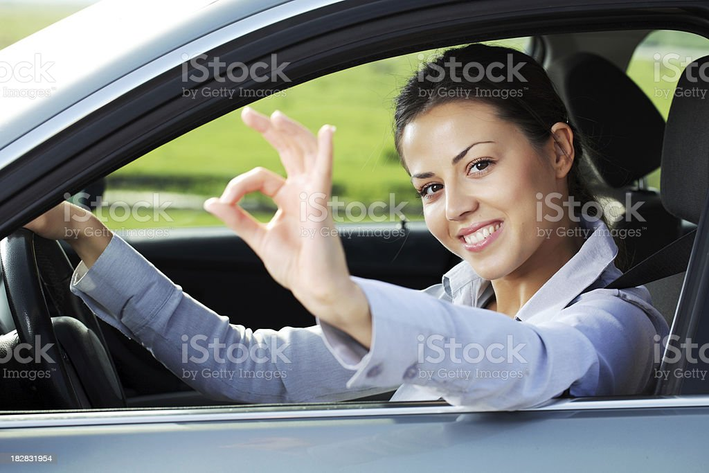 Business woman through the car window showing ok. royalty-free stock photo