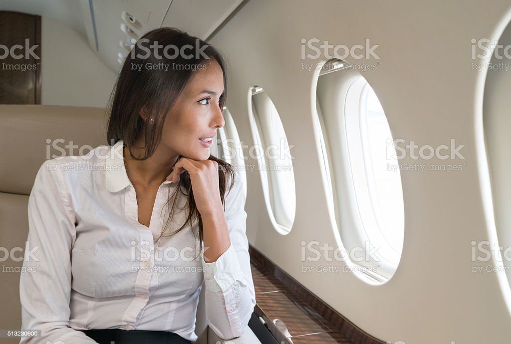 Business woman traveling by plane stock photo