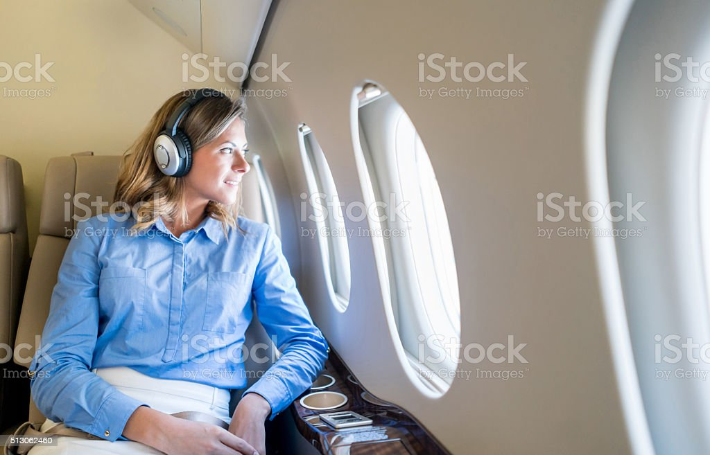 Business woman traveling by plane wearing headphones stock photo