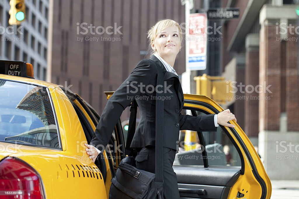 Business woman traveling by yellow taxi in city royalty-free stock photo