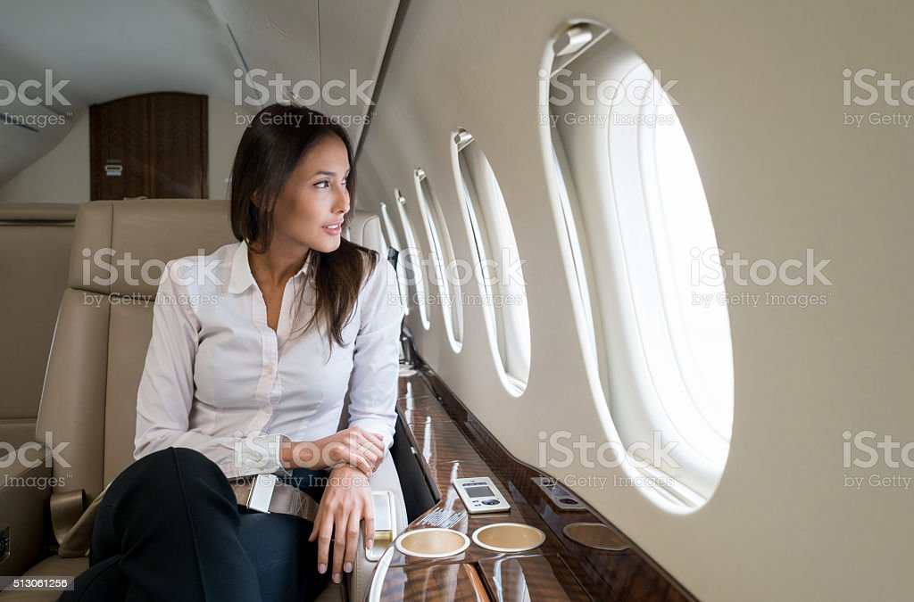 Business woman traveling in a private jet stock photo