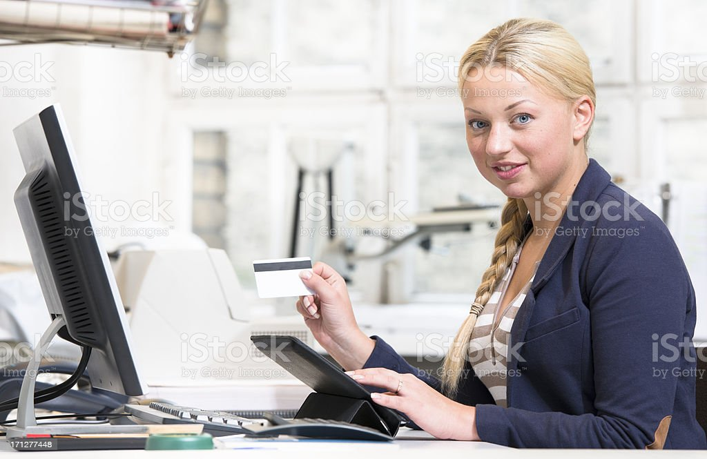 Business woman typing on digital tablet and using credit card stock photo