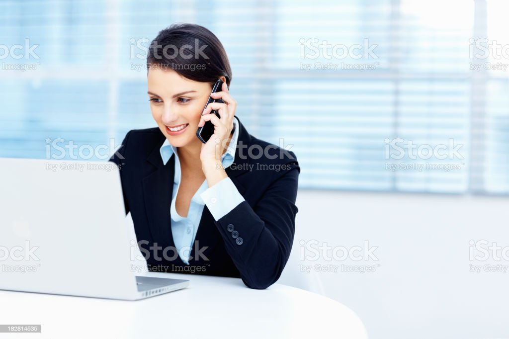 Business woman using cellphone and laptop in office royalty-free stock photo