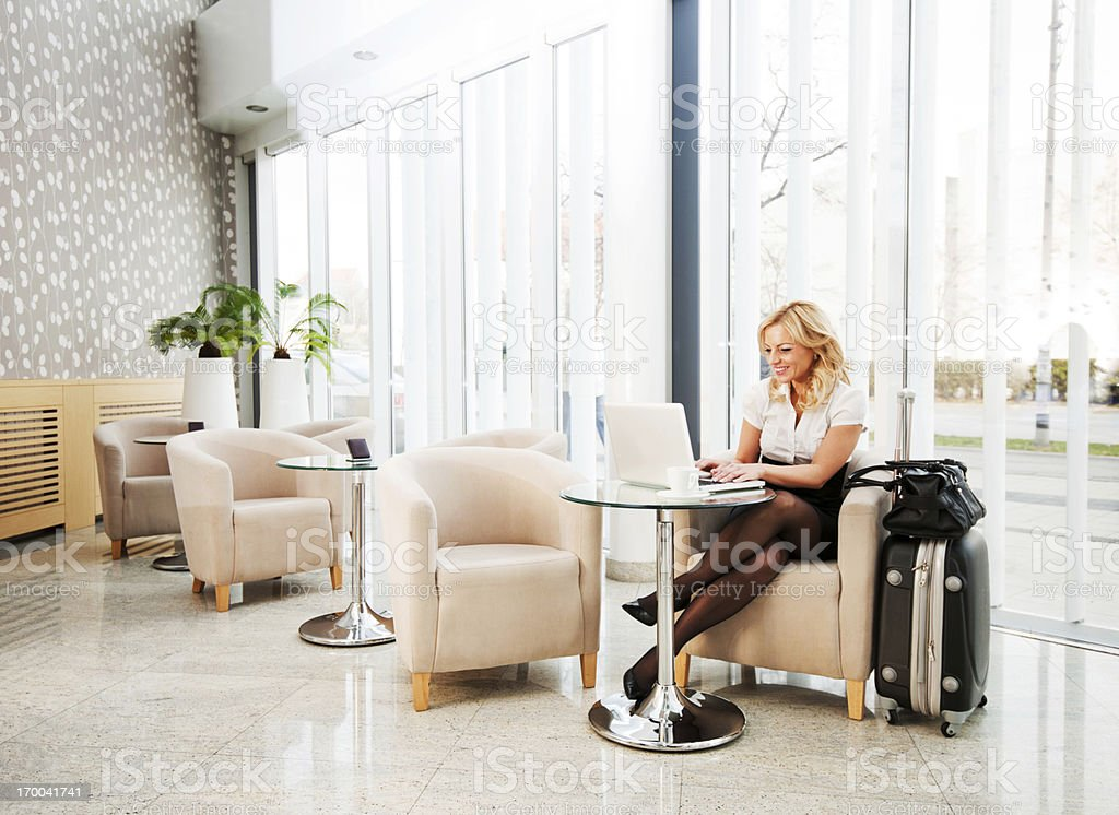 Business woman using her laptop in a hotel lobby. stock photo