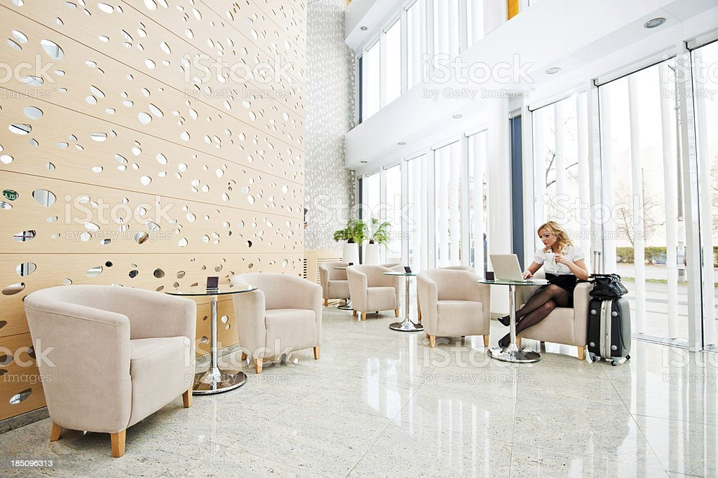 Business woman using her laptop in a hotel lobby. royalty-free stock photo