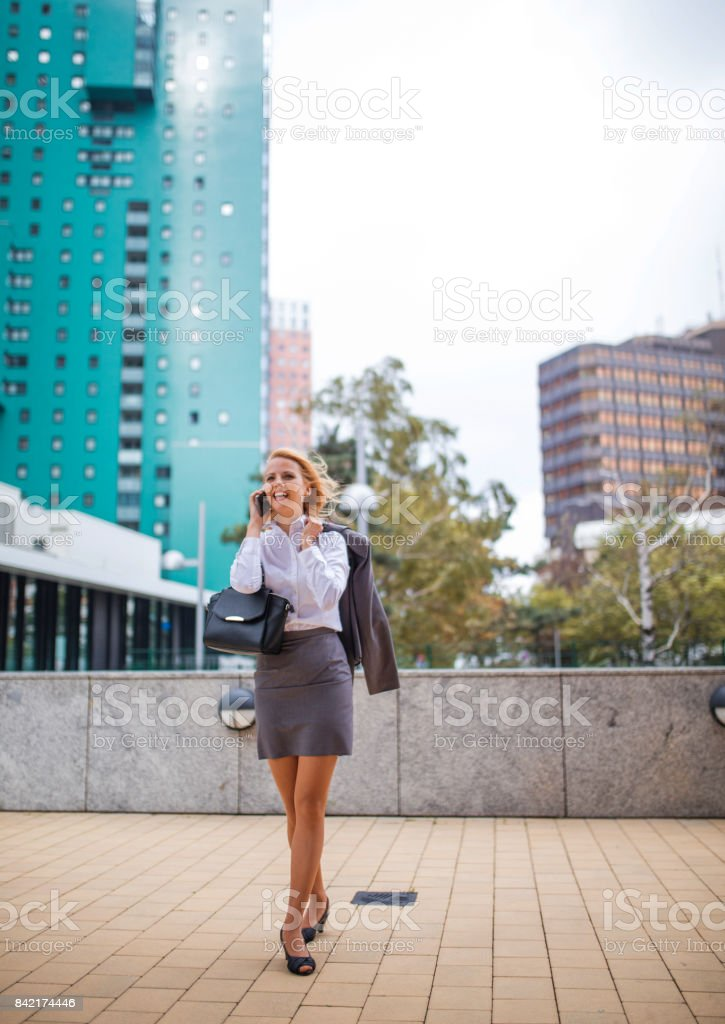 Business woman using phone while walking