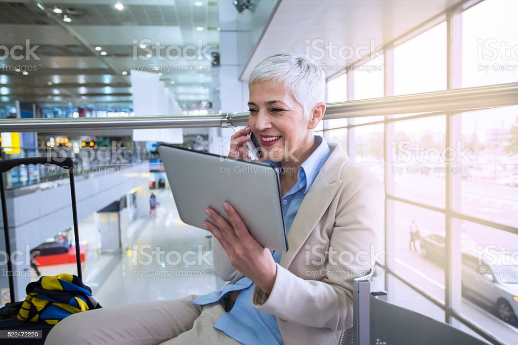 business woman waiting for her flight in airport lounge stock photo