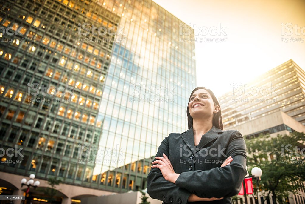 business woman with arm crossed in front of a buiding stock photo