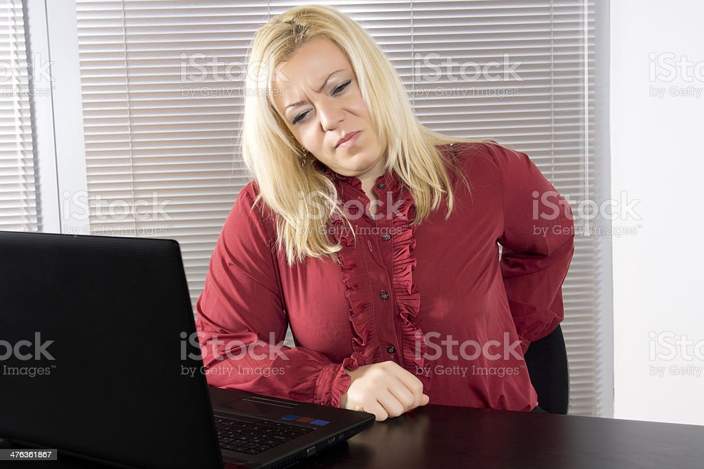 Business woman with back pain sitting at computer stock photo