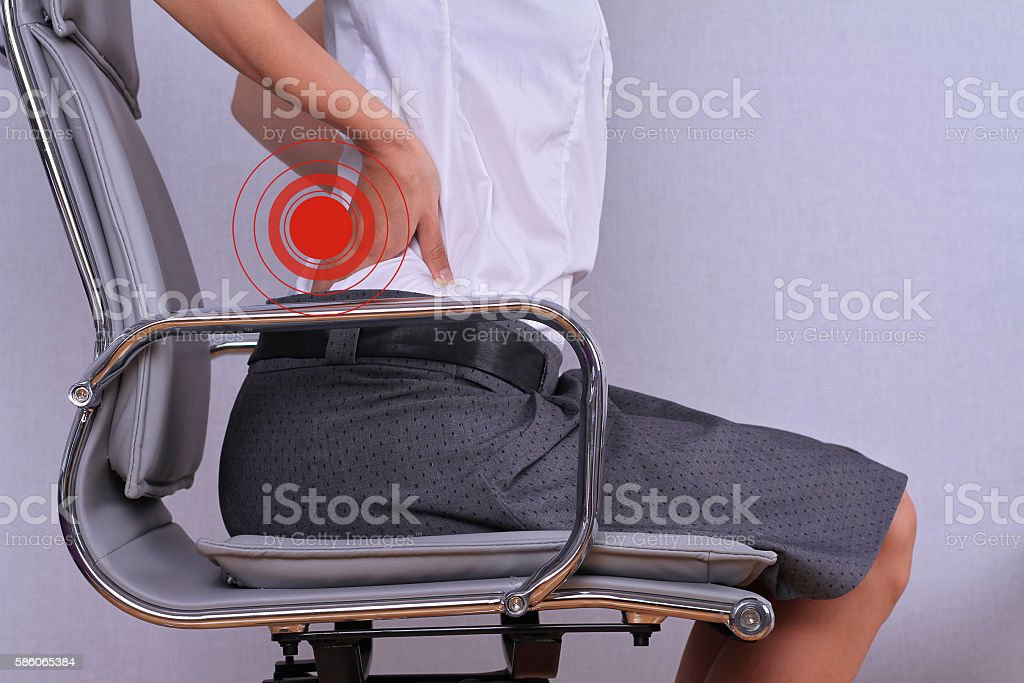 Business woman with back pain sitting in an office chair. stock photo