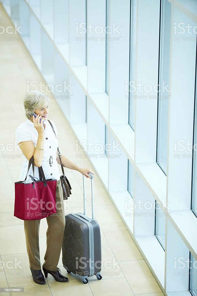 Business woman with baggage's using cell phone in an airport stock photo