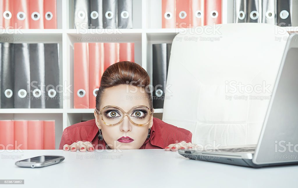 Business woman with big eyes hiding behind table stock photo