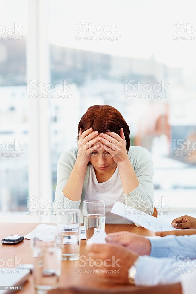 Business woman with headache sitting in a meeting royalty-free stock photo