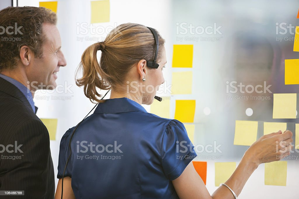 Business woman with headset explaining work schedule to male colleague royalty-free stock photo
