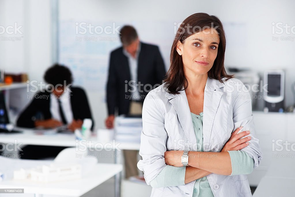 Business woman with her hands folded with business colleagues working at the back stock photo