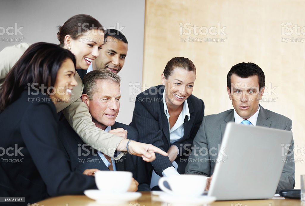 Business woman with her team pointing at laptop in meeting royalty-free stock photo