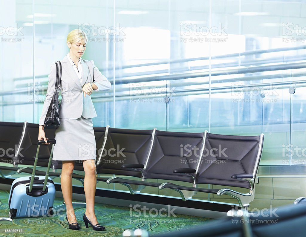 Business woman with luggage looking at watch in an airport stock photo