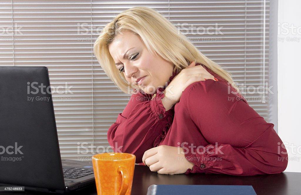 Business woman with neck pain sitting at computer stock photo