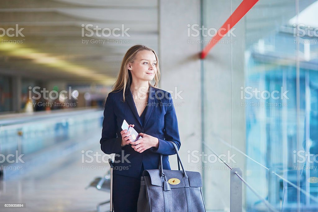 Business woman with passport and boarding pass in international airport stock photo