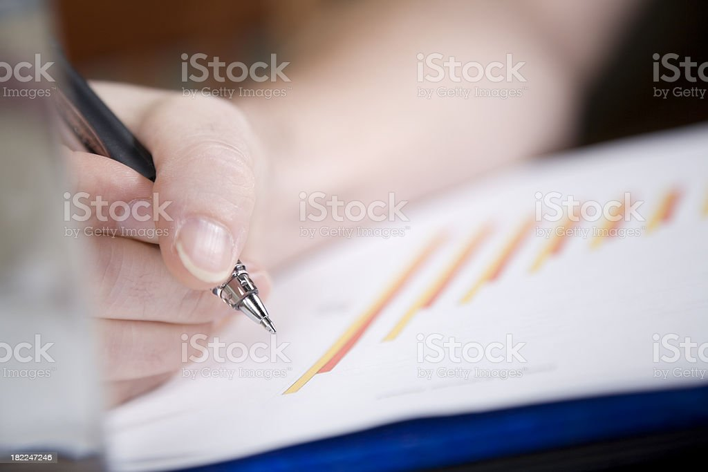 Business Woman with Pen to Company Financial Charts royalty-free stock photo