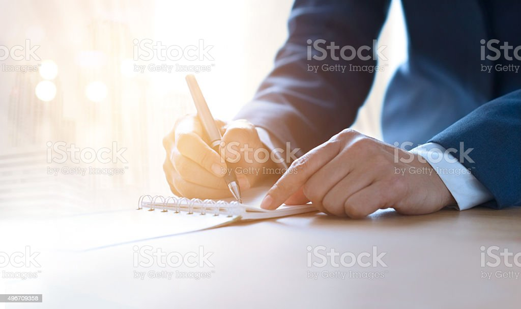 Business woman with pen writing on notebook in vibrant lighting stock photo