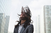 Business woman with wind in hair in urban environment