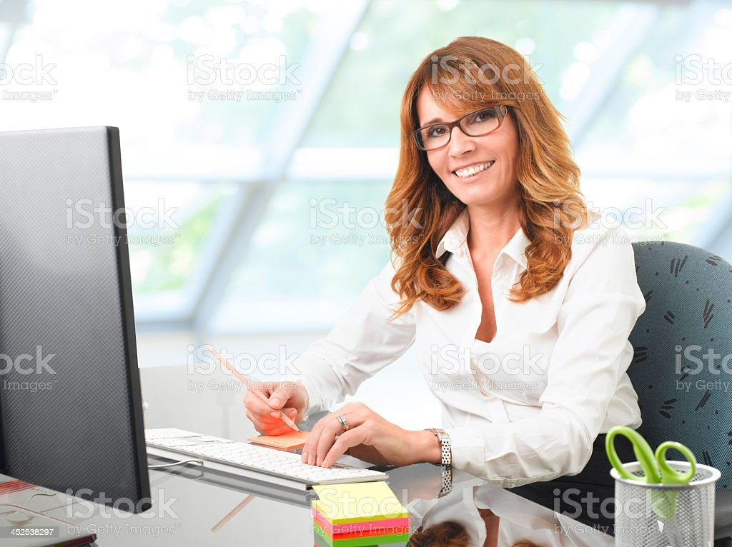 A business woman working at her office desk stock photo