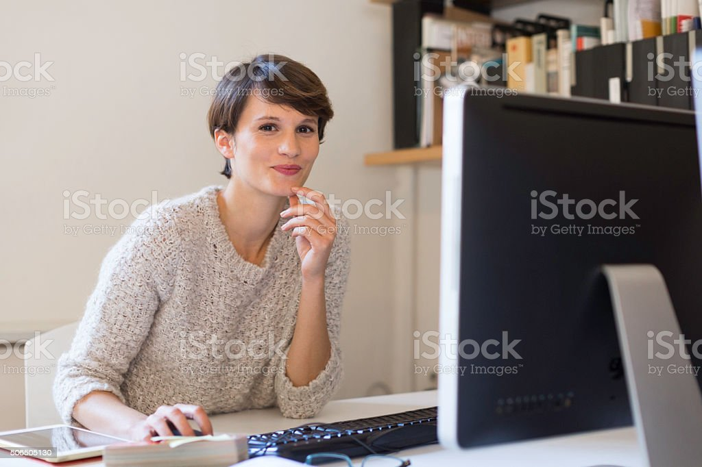 Business woman working in small office, Barcelona. stock photo