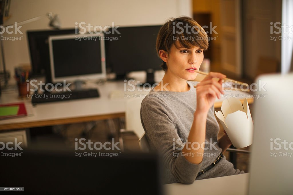 Business woman working late in small  office, Barcelona. stock photo