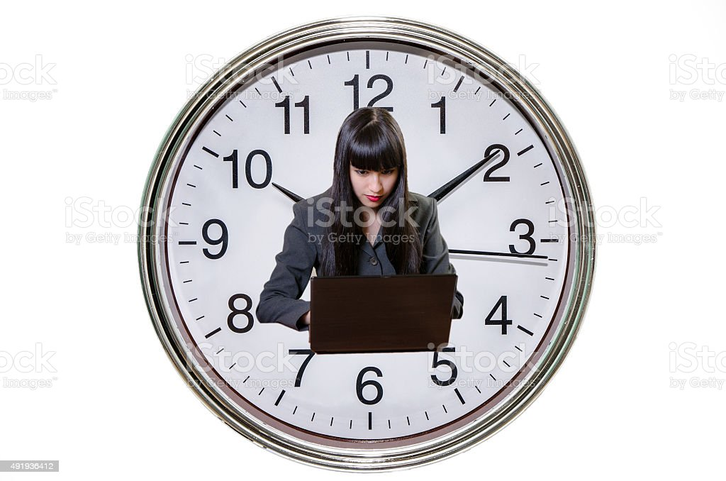 Business woman working on laptop and big clock background stock photo