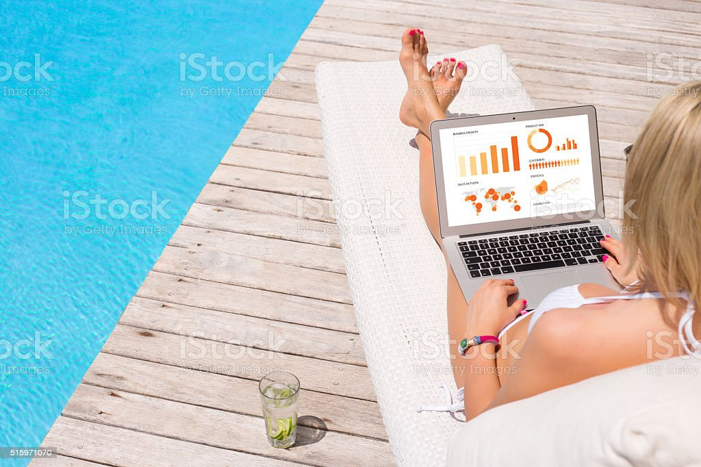 Business woman working with laptop by the pool stock photo