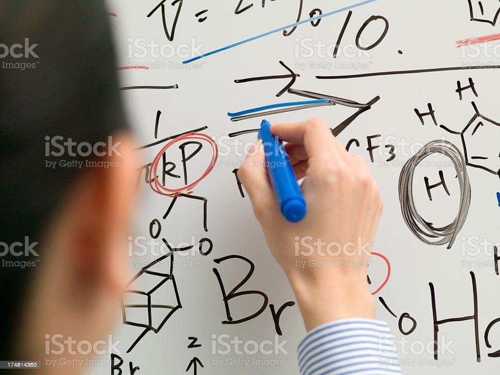 女性実業家はペンでホワイトボードで書き込むBusiness woman writes on the whiteboard with a pen. royalty-free stock photo