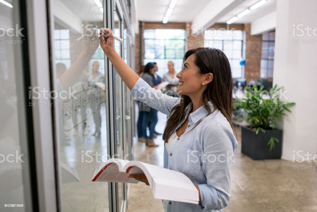 Business woman writing ideas on the board stock photo